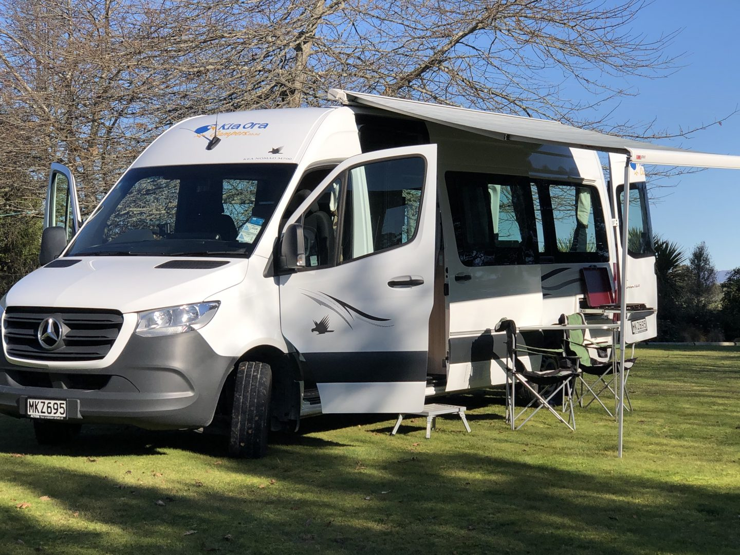 campervan with tables and chairs under awning